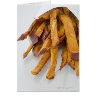 A batata doce frita no saco de papel, fim acima, cartão