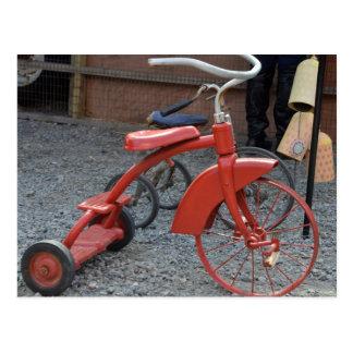 A bicicleta vermelha do triciclo do vintage deixa cartão postal