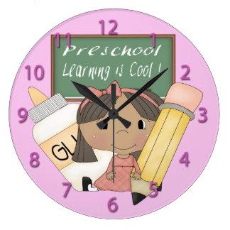 A menina étnica pré-escolar que aprende é pulso de relógios de paredes