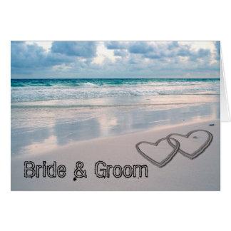 A noiva & o noivo nomeiam escrito na areia cartão comemorativo