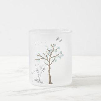 Árvore com as flores no fundo azul caneca de vidro fosco