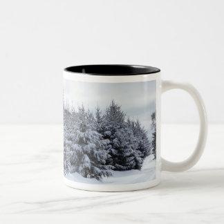 Árvores e estrada verdes na neve canecas