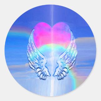 Asas do anjo envolvidas em torno de um coração adesivo