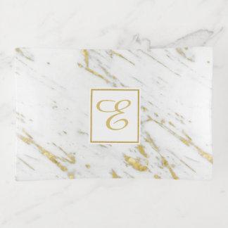Bandejas Quadro e brilho manchados do ouro sobre o mármore