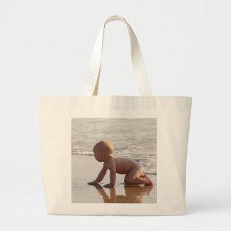 Bebê que joga na areia na praia bolsa de lona