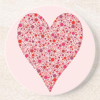 Bolinhas carmesins da forma do coração no rosa porta copos de arenito