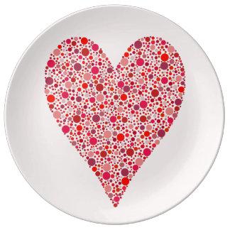 Bolinhas carmesins da forma do coração no rosa pratos de porcelana