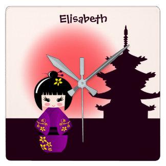 Boneca japonesa do kokeshi no templo durante o por relógio quadrado