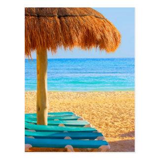 Cabana & Loungers da grama na praia Cartão Postal