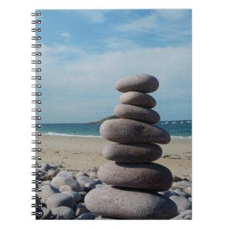 Caderno Espiral Escultura do seixo em uma praia