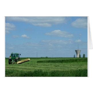 campos de trigo do corte do trator e uma torre de  cartao