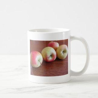 Caneca De Café Quatro maçãs maduras na mesa de madeira