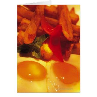 Cartão fim-acima dos ovos fritos com batatas fritas