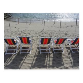 Cartão Postal Fileira de cadeiras de madeira coloridas na praia