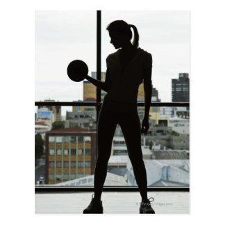 Cartão Postal Silhueta de pesos de levantamento da mulher no gym