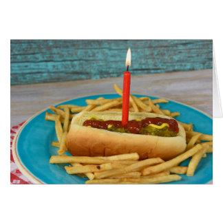 Cartão vela do aniversário no cachorro quente com batatas