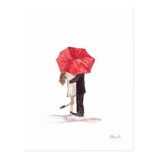 Casal no amor sob o guarda-chuva vermelho cartão postal