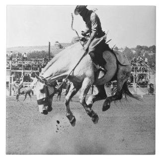 Cavalo bucking da equitação do homem no rodeio azulejos