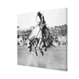 Cavalo bucking da equitação do homem no rodeio impressão de canvas envolvida