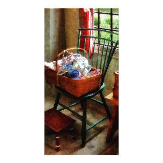 Cesta do pano e do fio na cadeira cartao com foto