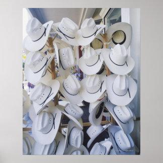 Chapéus de vaqueiro que penduram em uma loja de ch poster