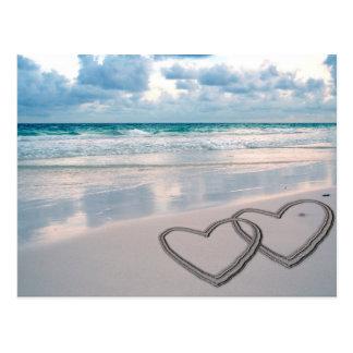 Corações tirados na areia cartões postais