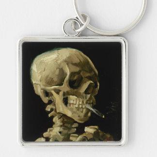 Crânio de um esqueleto com o cigarro ardente por chaveiro