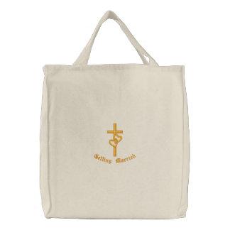 Cruz com a sacola entrelaçada dos corações bolsas