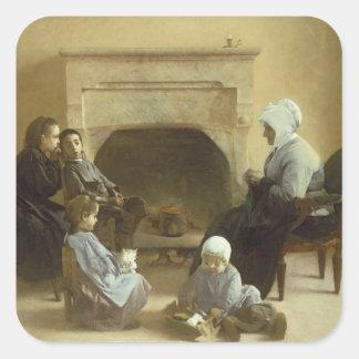Família assentada em torno de uma lareira adesivo quadrado