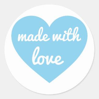 Feito com design de texto do amor no coração azul, adesivo