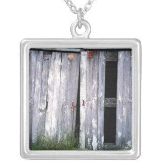 Foto velha dos celeiros das construções das portas colar banhado a prata