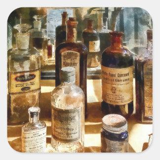 Garrafas da medicina no caso de vidro adesivo quadrado