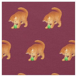 Gato alaranjado do gatinho que joga com tecido da