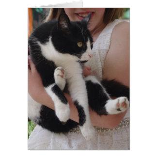 Gato preto e branco com cartão da criança