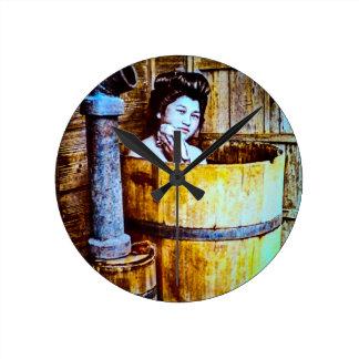 Gueixa japonesa do vintage que banha-se em uma relógio redondo