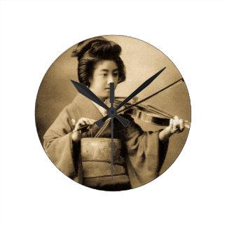 Gueixa japonesa do vintage que joga o clássico do relógio redondo