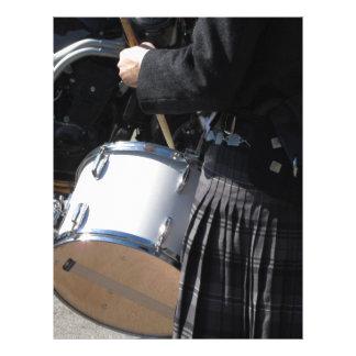 Homem com o kilt que joga em cilindros papel timbrado