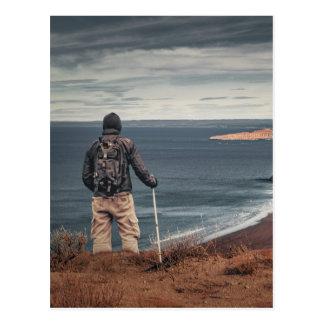 Homem em elevações que contempla a paisagem cartão postal