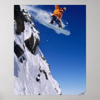 Homem em um snowboard que salta fora de um cornice poster