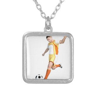 Jogador de futebol em alaranjado, em amarelo, e o colar com pendente quadrado