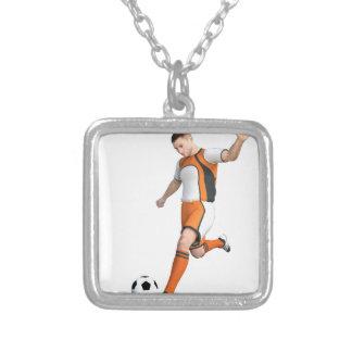 Jogador de futebol em alaranjado, em preto, e o colar com pendente quadrado