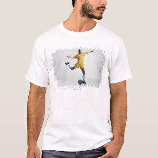 Jogador de futebol fêmea que prepara-se para camisetas