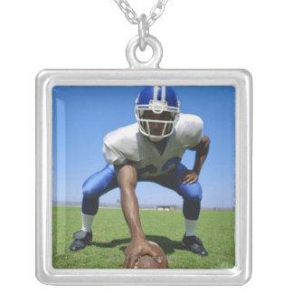 jogador de futebol que joga em um campo de futebol colar com pendente quadrado