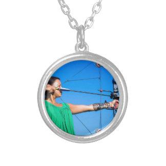 Jovem mulher que aponta a seta do arco composto colar banhado a prata
