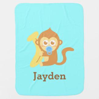 Macaco bonito do bebê com a cobertura do bebê da mantas para bebe