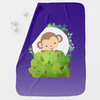 Macaco bonito do safari com as folhas tropicais no cobertor para bebe