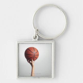 Mãos que guardaram um basquetebol fim-acima das m chaveiros