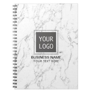 Mármore branco elegante do logotipo feito sob cadernos espirais