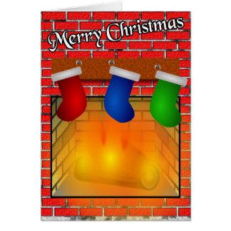 Meias sobre um cartão de Natal da lareira