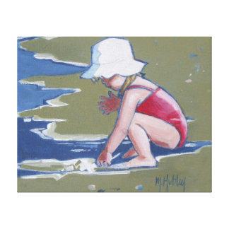 Menina com o chapéu na praia com ondas